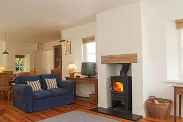 The big sitting/dining-room has a warming wood-burner and sea and beach views.