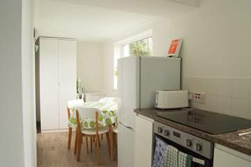 The modern kitchen with dining space, the little garden area for the property can be seen just outside the kitchen window.