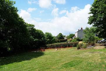 The view across the shared garden towards the Owners' cottage seen amongst the trees on the right.