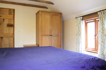 This bedroom also has a good amount of storage with solid wood furniture.