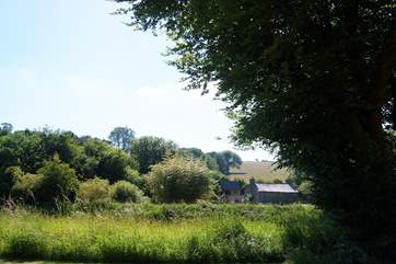 Looking across the river to an old cottage and barns on the other side.