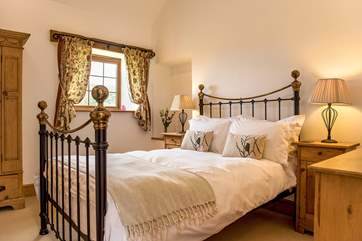 Bedroom 2 has a gorgeous brass bed, bright white linen and an en suite shower-room.