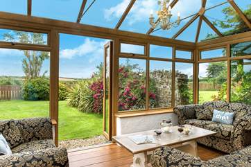 The sunny conservatory enjoys wonderful views over the garden.