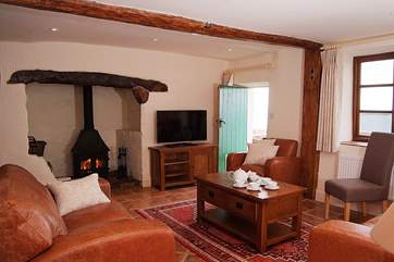 The sitting-room has a wood-burner, deep comfortable sofas, lovely tiled floors and a rich rug. The door has a curtain so can be closed off for a snug evening.