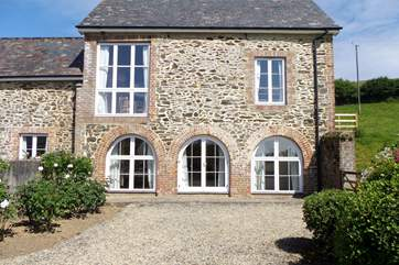 The master bedroom has the three ground floor windows, the open plan living area and kitchen are above and to the left-hand side of this building encompasses the entrance hall and second bedroom.