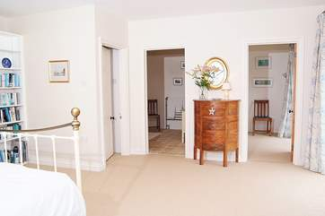 At the far end of this spacious bedroom is an en suite bathroom and a separate dressing-room or cot-room.