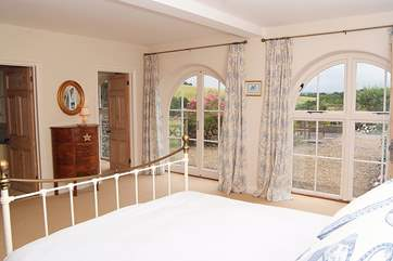 Floor to ceiling glass doors bring in the light and the countryside views, and direct access to the front garden area.