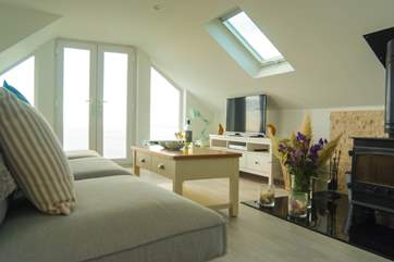 The living-room is flooded with light from windows, French doors and Velux skylights.