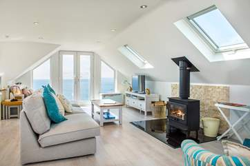 The living room is flooded with light thanks to the patio doors and velux skylights