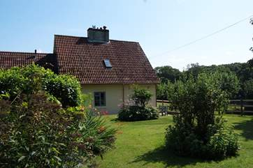 The cottage is set to one side of its gardens and has lovely views across the fields.