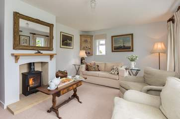 The calm and elegant living room has a wood burning stove for out of season holidays. This dual aspect room looks out over the fields.