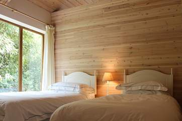 The twin bedroom with 3ft single beds and open roof up to the wooden beams above.