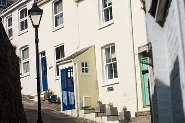 Whistlefish (house with porch and blue door) is one of a terrace of four cottages on a very steep pedestrian hill.