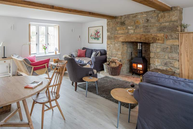 The open plan sitting/dining-room has three sofas to choose from and a cosy wood-burner.
