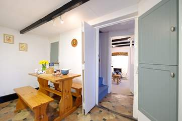 Looking from the kitchen through to the sitting-room, with steep cottage stairs leading to the first floor.
