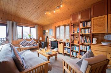 The open plan living-room has a wood-burner effect gas stove.