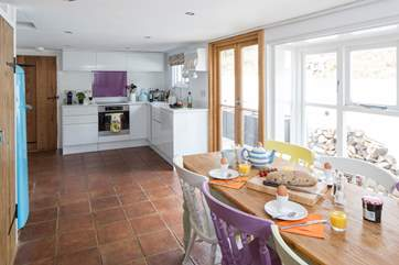 The open plan kitchen and dining-room is a very sociable space and has French doors onto a sheltered patio area.