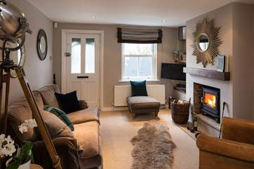 The sitting-area has luxurious furnishings and a cosy wood-burner, perfect for relaxing with a good book or a glass of wine.