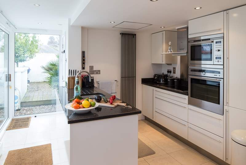 The well-equipped modern kitchen has all you need to conjur up something delicious; beyond is the downstairs shower-room.
