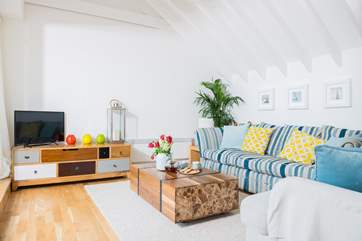 The vaulted living-room is tastely furnished with a comfy sofa and solid wood furniture.