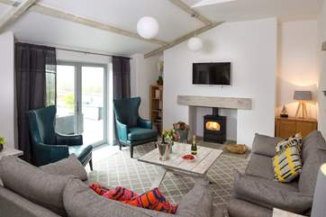 The comfy sofas and stylish armchairs flank the wood-burner. There is a short bannister to one side of the steps leading down into this room.