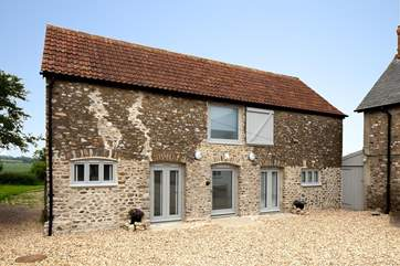 The Cow Shed is a superb top quality barn conversion with a huge terrace and hot tub at the back, and views for miles.