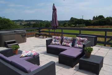 The terrace has wonderful rural views and a table and chairs as well as this relaxed seating for perfect outdoor living on a sunny day.