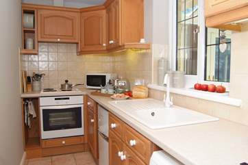 There is a bright,cheerful and very well equipped kitchen with extra  light coming through from the conservatory.