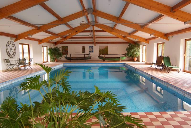 The heated indoor swimming pool is 13 metres long and 8 ft at the deep end. The tennis court can be glimpsed behind it.