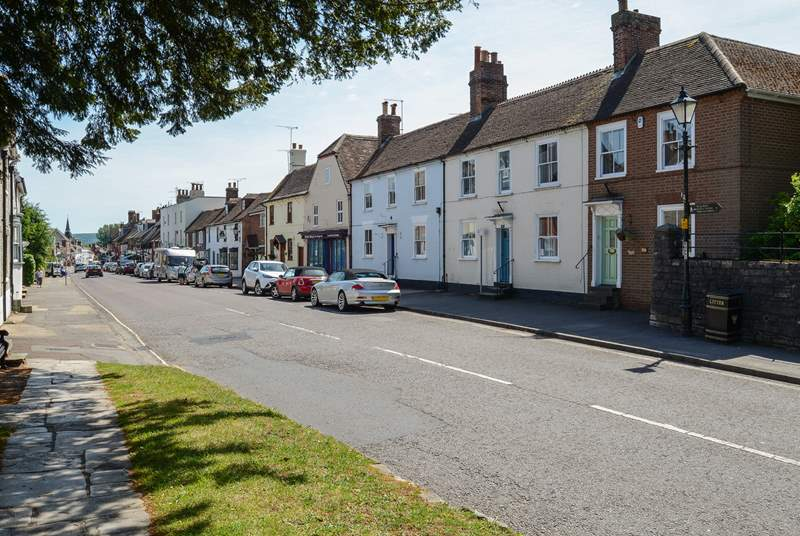 The pretty market town of Wareham, Northgate is in the foreground with the green front door and hanging basket.
