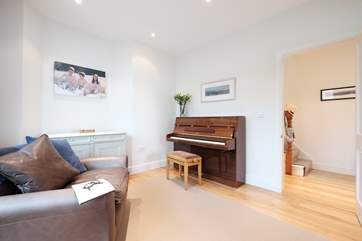 There is a piano at one end of the sitting-room.