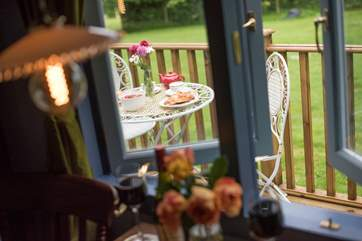 Looking through the dining-area window to the deck with table and chairs for al fresco dining.