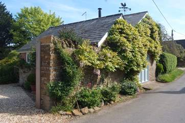 This lovely cottage is covered in wisteria blossom in the Spring.