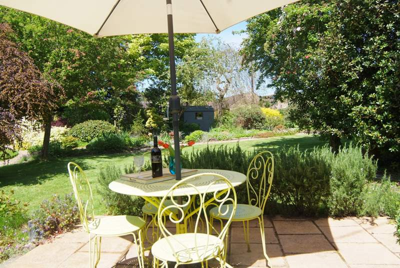 A  sunny patio is tucked away behind the Coach House. It overlooks the lovely gardens here and feels nice and private