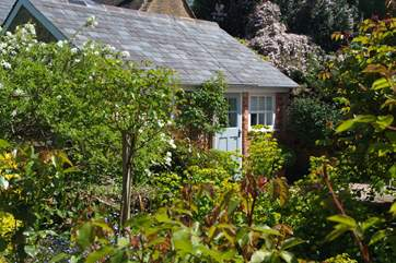 The cottage is surrounded by beautiful shrubs and plants, giving a good sense of privacy.