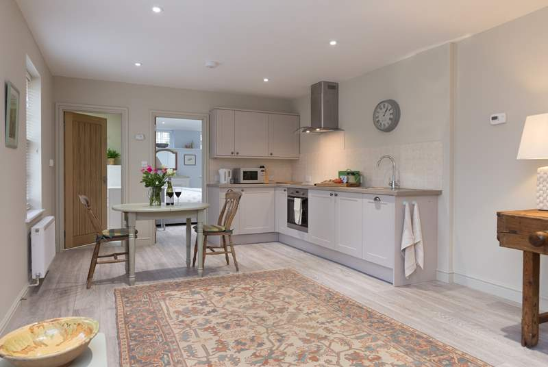 The open plan living area has a kitchen tucked at one end and plenty of space for a dining table and for the comfortable sofa and armchair too.