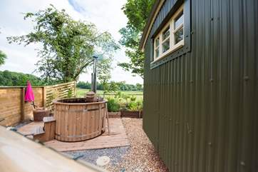 The wood-fired hot tub is positioned in a private spot to the side of the hut but fully screen fenced for privacy.