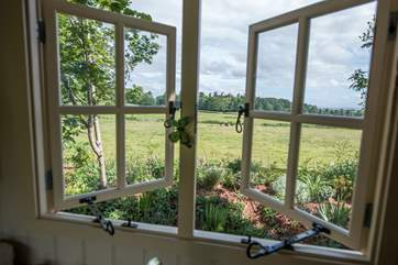 The view from your kitchen window across open fields which are grazed with cattle and sheep.