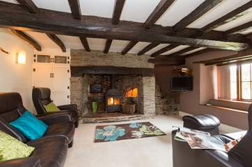 The cosy sitting-room with its wood burnng stove and characterful beams. Reclining leather easy chairs and sofa will help you to relax at the end of the day.
