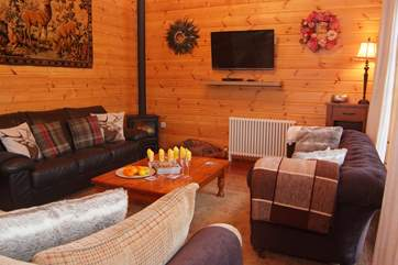 The cosy seating area has an electric wood burner effect stove and three