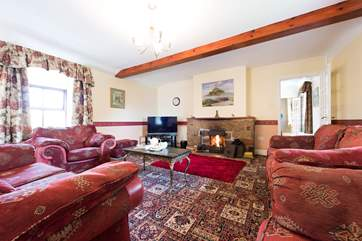 The huge sitting-room has a roaring open-fire.