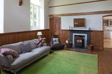The spacious sitting room with a warming wood-burner.