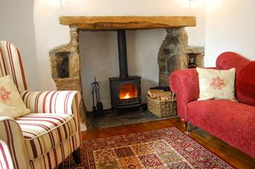 A wood-burner in the original inglenook fireplace keeps the cottage toasty warm.