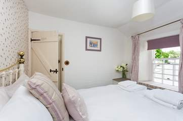 The master bedroom is furnished in soft pastels.