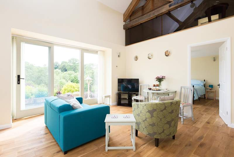 The lovely double height open plan living area has French windows out onto the terrace.