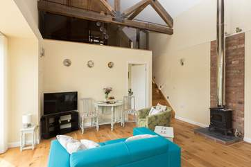 The second bedroom is up the stairs in one of two mezzanine areas. The wood-burning stove is ornamental - but the Studio is so snug in any case.