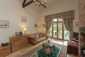 The living room has French windows to the patio and the large enclosed garden beyond.