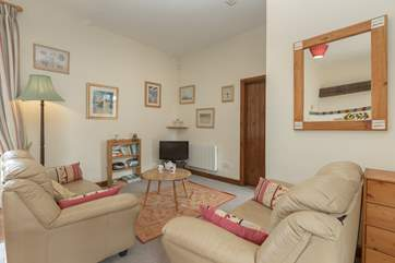 This is the cosy living room part of the open plan ground floor.  The door in the photograph is to the main bedroom
