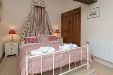 This is the master bedroom.  The bed offers a touch of luxury to the feel of the room, which overlooks the large enclosed garden