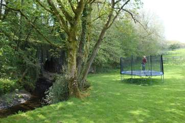 Trampoline sits along the side of the stream, endless fun for all the family. However, please take care.